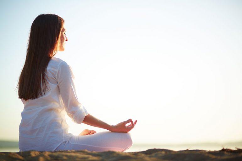 donna medita sulla spiaggia