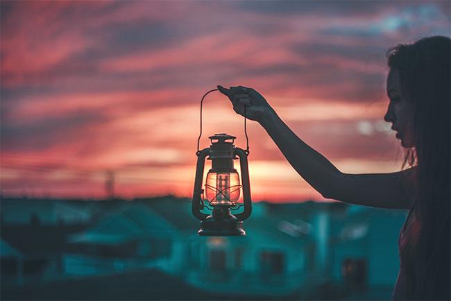 girl holds lantern at sunset