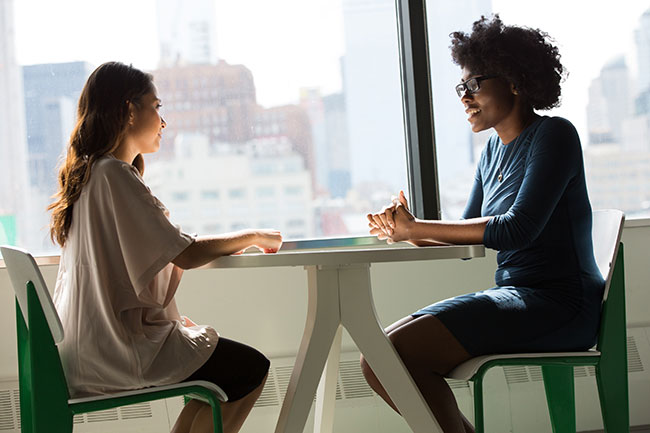 two women sitting opposite each other are having conversation