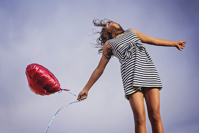 happy woman jumps in the air holding a heart-shaped balloon