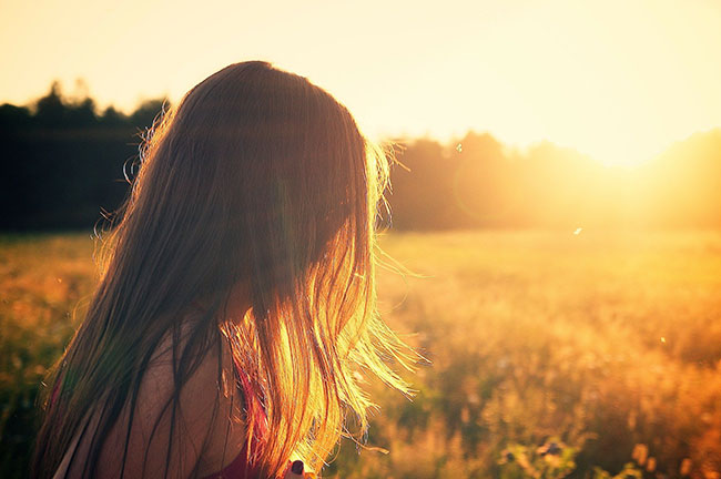 woman from behind observes a summer sunset